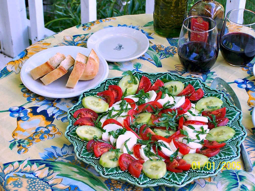 Caprese Salad. A summer salad of fresh mozzarella, fresh home grown tomatoes and english cucumber. Topped with fresh basil leaves.
