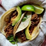 Achiote shredded pork tacos with avocado served in soft corn tortillas garnished with cilantro leaves