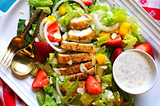 Fried chicken breast salad with sliced strawberries, mango, onion, romaine, and poppyseed dressing