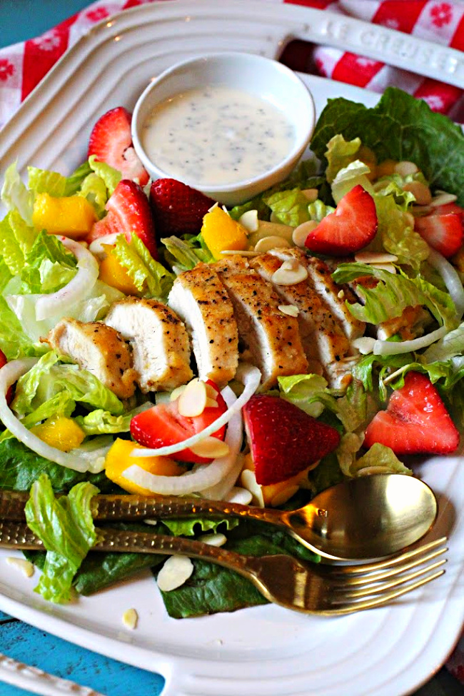 Fried chicken breast sliced on romaine lettuce with strawberries, onion, mango with poppyseed dressing