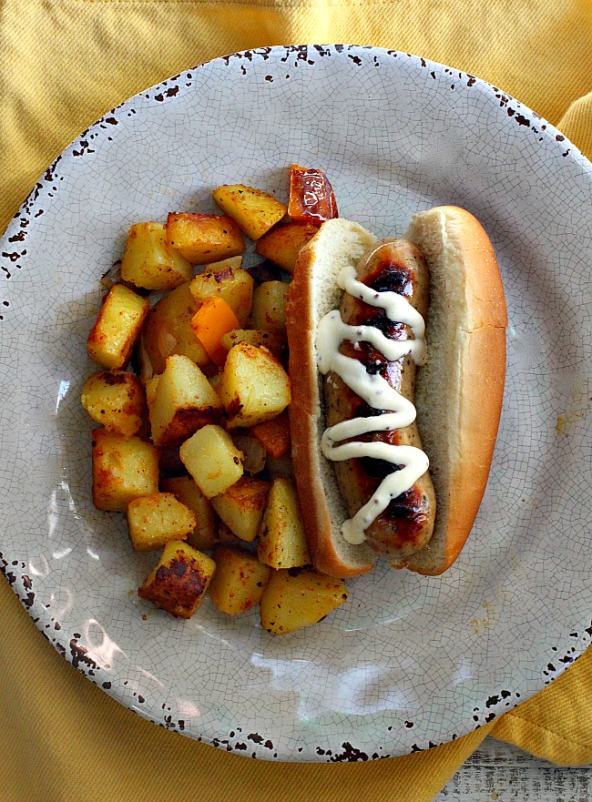 Chicken apple sausage hot dogs with mayonnaise mustard dressing served alongside country fried potatoes