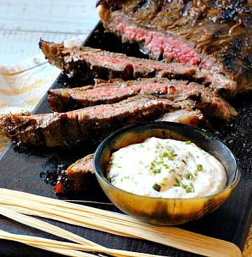 Marinated flank steak on a black wood cutting board with a bowl of horseradish cream sauce
