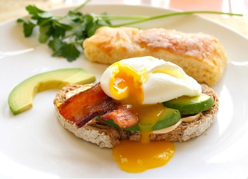 Breakfast Sandwich with chipotle mayo, bacon and avocado. Topped with a poached egg.