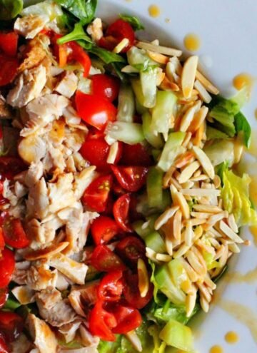Grilled Chopped Chicken Salad with chopped tomatoes, toasted almonds, cucumber, and a pineapple chile dressing