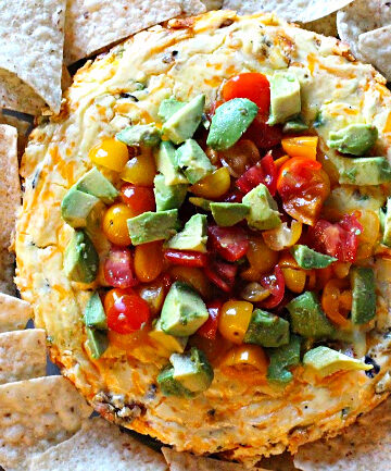 Mexican Cheesecake topped with tomatoes and avocado and surrounded by white corn tortilla chips