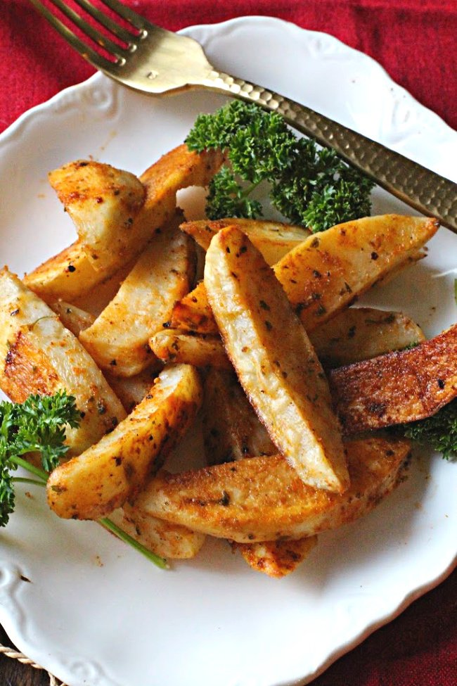 Oven Home Fries on an antique white platter with parsley as garnish.