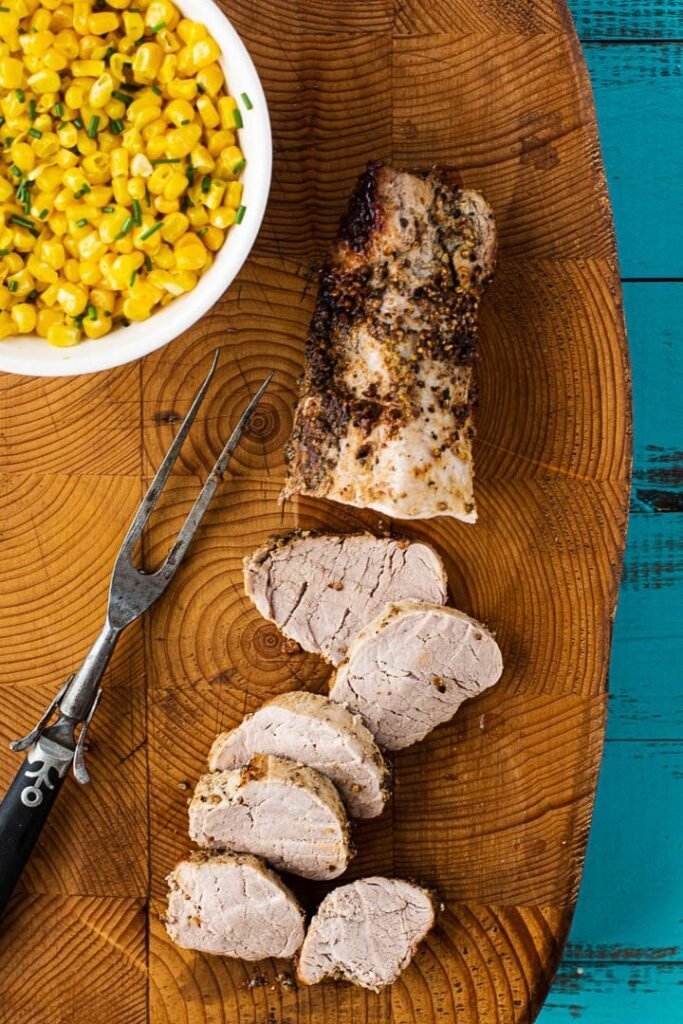 Baked pork tenderloin coated with dijon mustard and coriander and peppercorns. Sliced on a cutting board served with fresh corn.