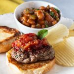 Lamb sliders topped with sweet tomato chutney and served with a bowl of baked beans.