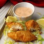 Marie Rose Sauce and pieces of battered cod on a bed of shredded iceberg lettuce with lemon wedges