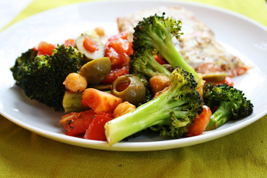 A side dish recipe for Mediterranean oven roasted broccoli with tomatoes, chickpeas, olives and capers.