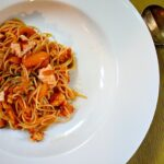 Angel Hair pasta with salmon and paprika wine sauce in a wide shallow white pasta bowl.