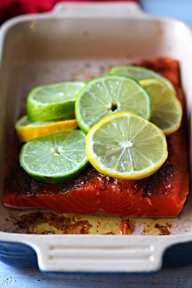 Lemon Lime Salmon in a Le Creuset baking dish topped with lemon and lime slices