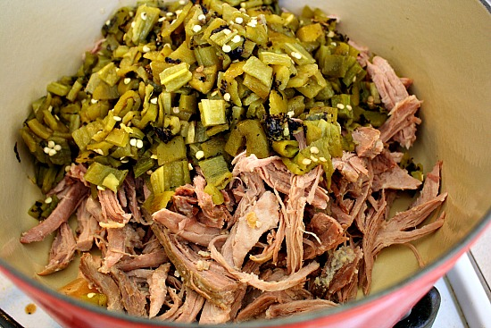 Shredded pork and roasted chopped hatch green chiles in a dutch oven ready to make hatch green chile colorado.