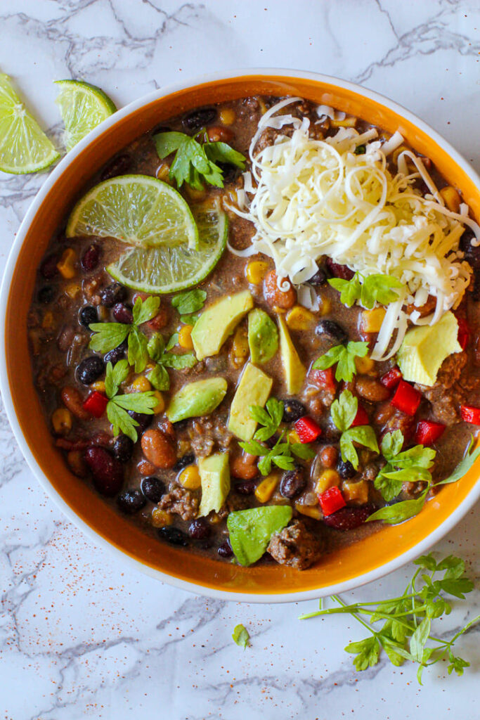 Bowl of Taco soup garnished with avocado, cilantro, lime slices and pepper jack cheese.
