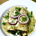 spinach chicken enchiladas topped with tomatillo cream sauce and red onion rings.
