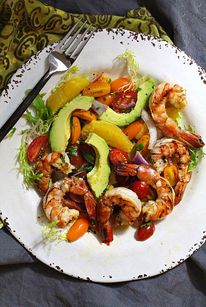 Grilled shrimp salad with avocado, orange wedges, mint and cherry tomatoes