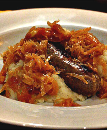 Brats and Kraut served over mashed potatoes
