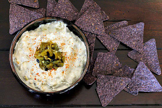Hatch green chile dip appetizer surrounded by blue corn tortilla chips