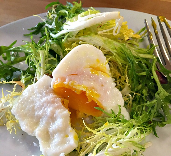 Green salad with poached egg and warm bacon vinaigrette