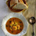 Bourride, French Cod and shrimp soup served in a white bowl with a side of french bread