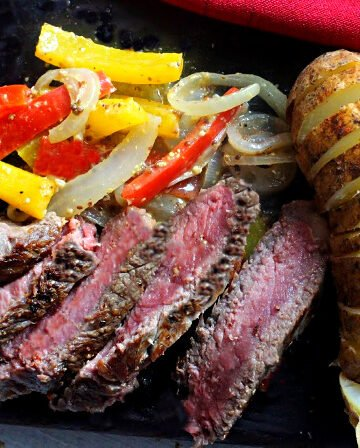Bison New York Strip steak with red and yellow bell peppers and a sliced baked potato