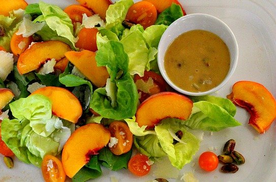 Butter leaf lettuce and fresh peach salad with pistachios and peach vinaigrette