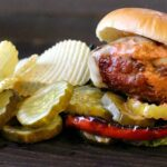 Bison burger with potato chips and spicy pickles.