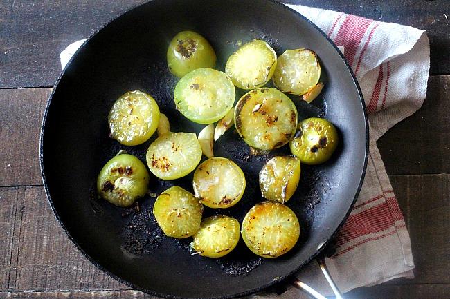 Roasting tomatillos in a pan with garlic to make Tomatillo Salsa Sauce.