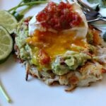 Potato cakes topped with guacamole poached egg and salsa