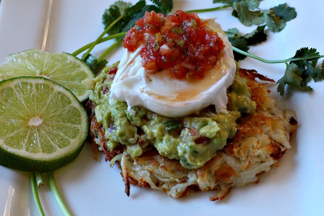 Hash Browns guacamole poached eggs breakfast with salsa on top.