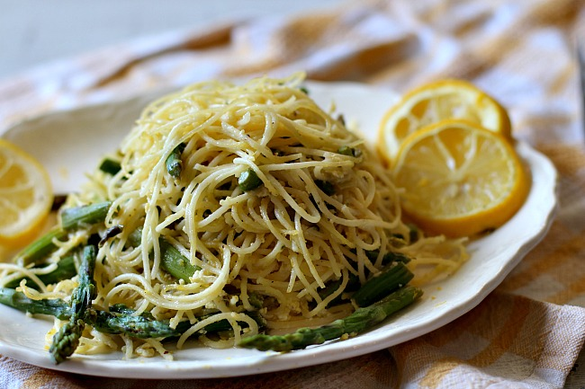 Angel Hair Pasta with Asparagus and lemon cream sauce on a white serving platter with slices of lemon.