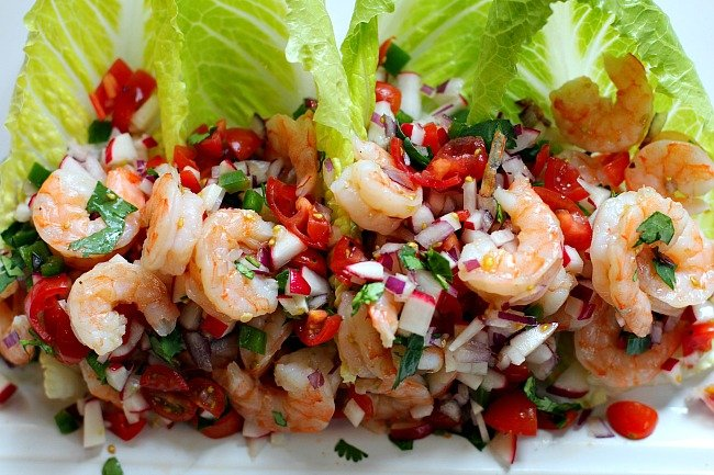 Shrimp tacos with tomatoes, radish, red onion on romaine lettuce with lime dressing