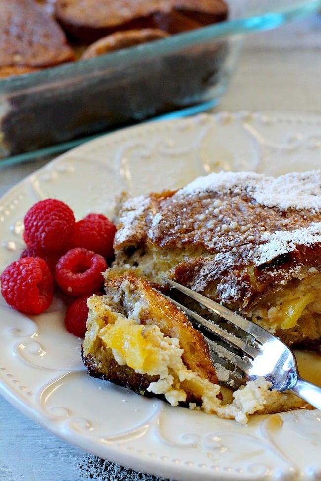 A slice of mango cream cheese stuffed french toast with a side of fresh raspberries