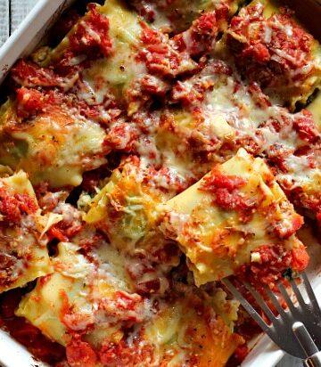 White casserole dish with chicken spinach lasagna rolls in tomato sauce, mazzarella and ricotta cheese