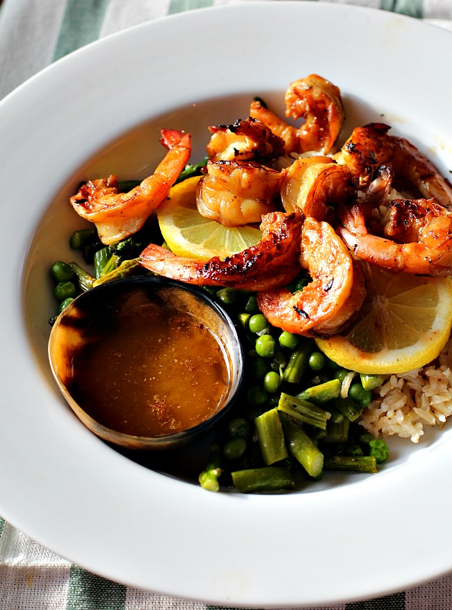 The best grilled shrimp recipe served over rice and asparagus with peas.