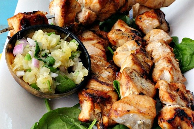 Grilled Chicken Kabobs on a white platter with fresh spinach and pineapple jalapeno salsa.