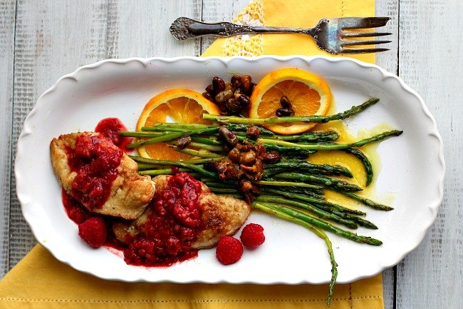 Chicken cutlets with raspberries, vinegar sauce and asparagus spears with orange sauce