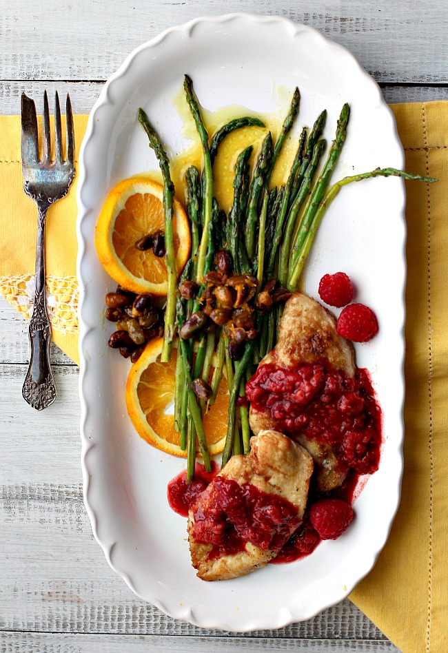 Chicken breast cutlets with raspberries sided with asparagus spears on oranges topped with pistachios