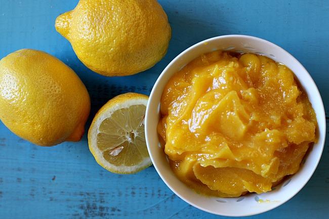 Homemade easy lemon curd recipe in a white bowl with fresh lemons