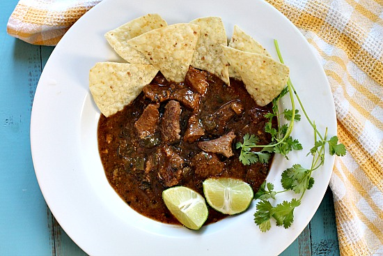Beef chuck chile recipe in a white bowl with lime and cilantro
