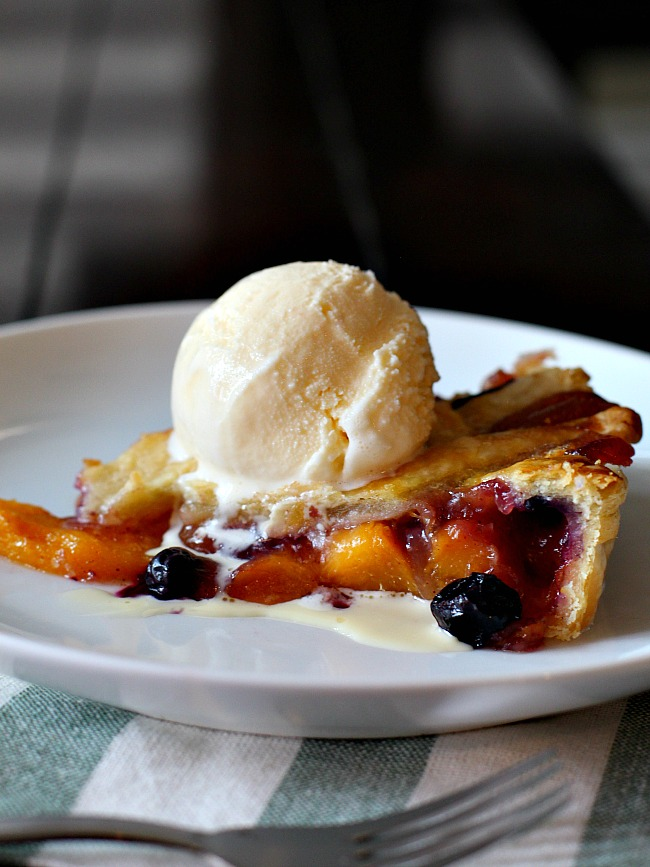 Slice of Peach Blueberry Pie topped with a scoop of vanilla ice cream.