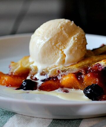 """peach blueberry pie in a 9"""" tart pan with lattice topping and topped with a scoop of vanilla ice cream"""