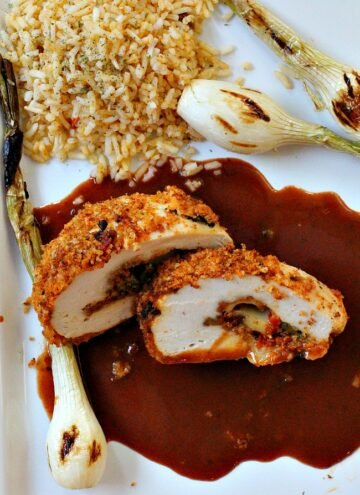 Chorizo cheese stuffed chicken breast with enchilada sauce, Spanish rice and grilled bulb onions