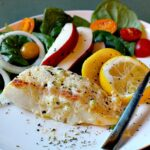 Baked Halibut Recipe topped with mayonnaise and served with a side salad