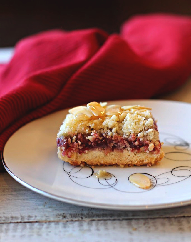 Raspberry bars made with almonds and raspberry jelly on antique tempo dessert plate