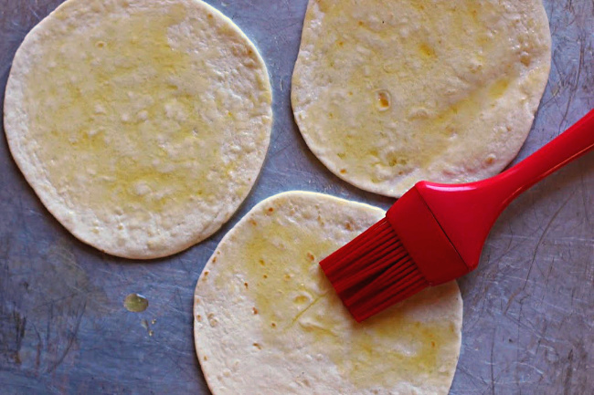Tortilla Pizza appetizer, oiling the flour tortilla with a silicone brush