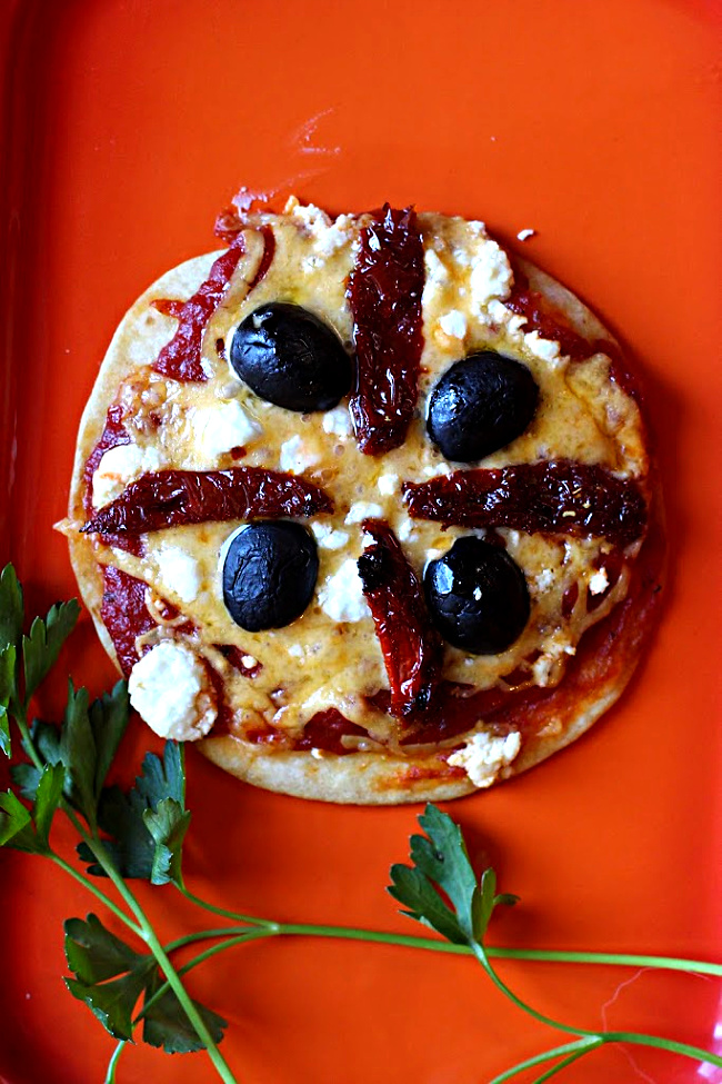 Tortilla pizza appetizer recipes. Flour tortilla topped with cheese, sun dried tomatoes, and olives.