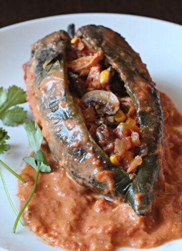 Chicken mushroom chiles rellenos with tomato cream sauce and cilantro.