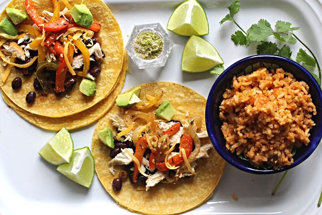Roasted bell pepper tacos with black beans and chicken served on a white le creuset platter