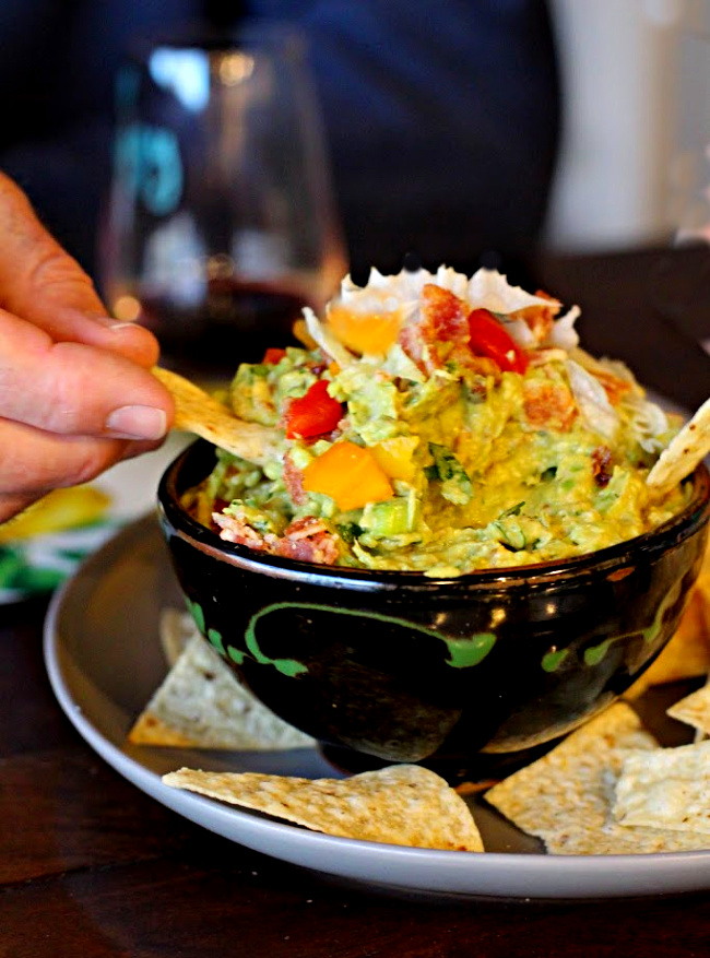 Spicy guacamole recipe served with corn chips and topped with bacon lettuce and tomato